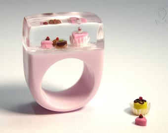Sweet pastries – extraordinary treats ring with a petit fours and 3 finest pralines on a pink ring with white lace made of resin