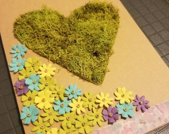 Blank greeting card with paper flowers and reindeer moss heart