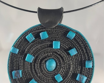 Round coiled polymer clay pendant in black and turquoise.