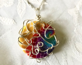 Rainbow colored stone wrapped in Silver Wire