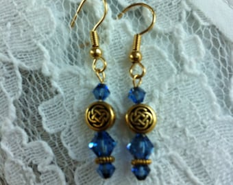Sapphire blue Swarovski and gold plated pierced earrings with Celtic knot beads.