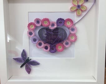 Quilled flower heart with additional flowers and butterfly. Comes already framed in a white 10 x10 inch box frame