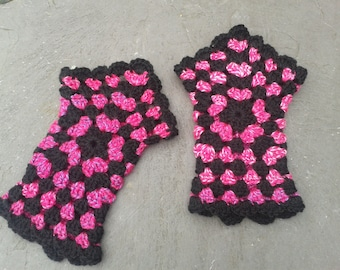 Crocheted pentagon wristwarmers, black and electric pink granny square design.