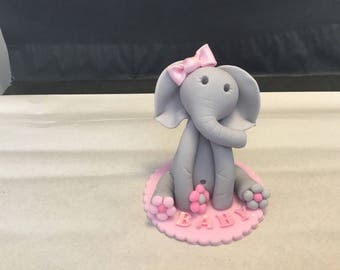 Pink baby elephant with base cake topper made out of fondant