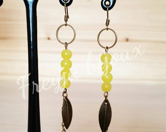 Yellow beads and leaf charms dangling earrings