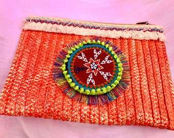 Clutch in orange with ethnic piece.