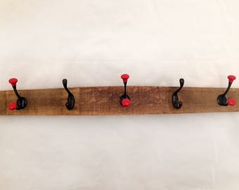 wall coat rack with red double hooks on a repurposed wine barrel stave