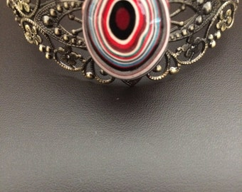 Ornamental cuff bracelet with fordite cabachon centerpiece