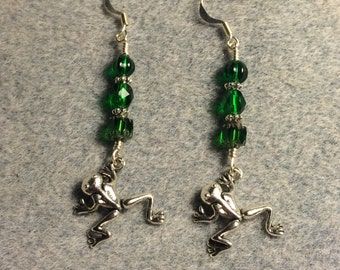 Small silver jumping frog charm dangle earrings adorned with emerald green Czech glass beads.