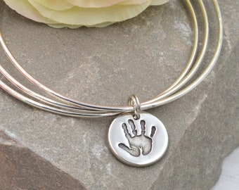 Handprint charm on a trio of bangles