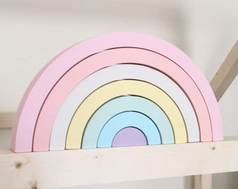 Pastel wooden rainbow stacking toy blocks.