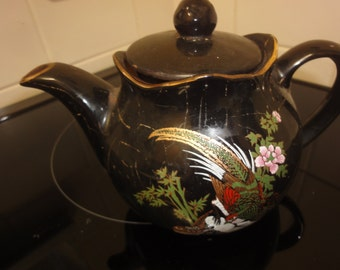 chinese tea pot in black with design embossed in gold