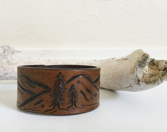 Mountain landscape with trees, leather cuff bracelet, stained brown