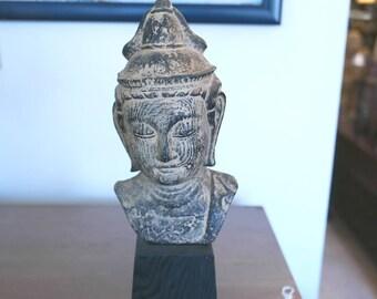 Bronze buddha head on an ebonized wooden base.