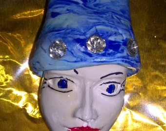Lady face brooch with bright blue swirl hat