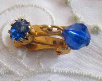 Vintage Gold Tone Medium Dark Blue Faceted Rhinestone Clip On Earrings with Iridescent Blue Glass Bead