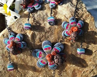 Set pink, blue and gray flowers with their turtle made of polymer clay.