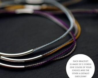 A solid silver tubular silk cord bracelet