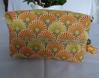 Makeup bag in golden orange tones of shape square;