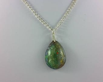 Necklace: blue-green teardrop resin pendant on silvery chain