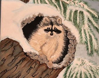 Hand painted cute little raccoon inside a log on a snowy day.