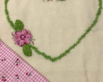 Cream wool blanket with crotchet flowers and hand embroidery. Backed with a cotton patterned fabric.
