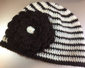 Knitted white-brown hat with a large flower
