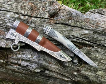 Small pattern welded knife with historically inspired, stamped silver and leather sheath.