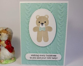 New baby boy card with teddy bear and cable knit embossed background in blue