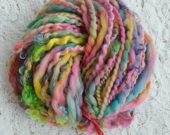 Altair skein of handspun wool with spinning wheel.