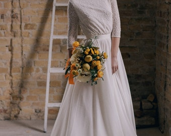 Off-white modest wedding dress with 3/4 sleeve lace bodice