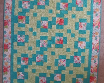 Cheerful lap quilt with hints of green, teal, fuchsia and pink.