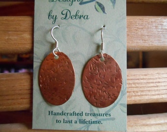 Oval, hammered copper dangle earrings with sterling silver ear wires.