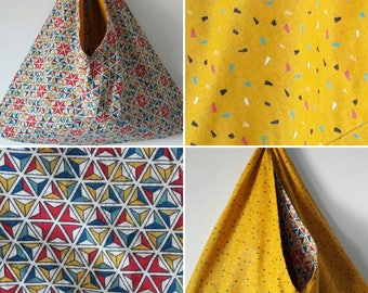 Reversible origami bag, a multicolored geometric patterned front and the other side yellow.