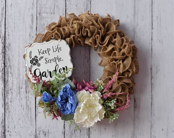 Burlap Wreath with blue, cream and pink flowers and a vintage rustic sign