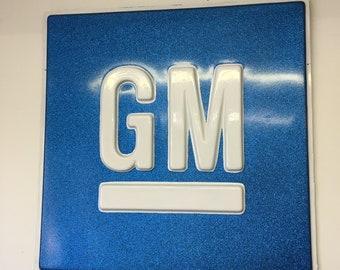 "Blue old school metal flake ""GM"" sign"