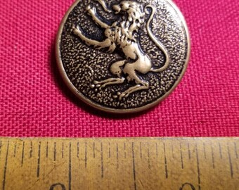Single large brass coat button with a lion rampant
