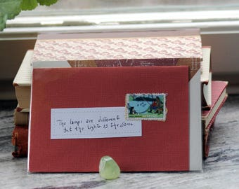 The lamps are different but the light is the same Dark terracotta card with handwritten quote and Swedish postal stamp
