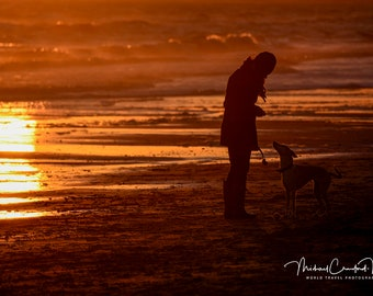 Silhouette of a Woman Dog on the beach at Sunset (Orange glow with sand, waves and sun)