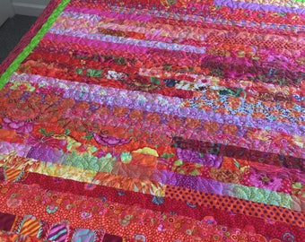 FIESTA SIESTA,  Queen quilt in Bright oranges and reds with a touch of purple and other colors