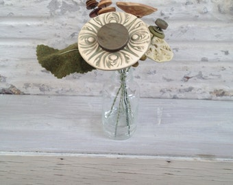 light brown, light green, and pale green button flower bottle bouquet