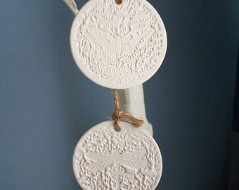 White clay wall hanging with butterfly and dragonfly design. Pair of clay tags hung with natural twine. Debbie Moore designs.