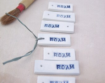Roam. Fired Clay Tags That Say Roam. Set of Seven. Hand Made. Recycled Clay.  With Blue Letters.