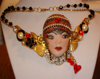 Upcycled, repurposed, one of a kind necklace. Red, black and gold tone, on double chain.