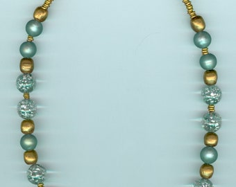 """Handmade necklace, one of a kind. Swirled glass focal, black, gold and blue, surrounded by blue and gold accents. L: 18 1/4""""."""