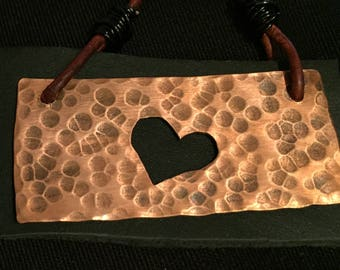 Hand cut and hammered copper necklace with heart cutout oxidation and leather patch