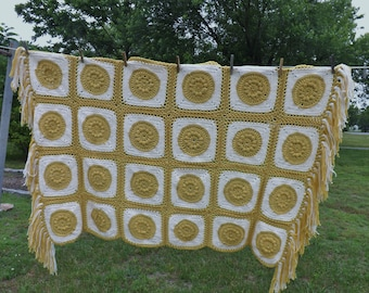 Delightful hand crocheted afghan in vanilla and gold featuring gold, circular puffy medallions