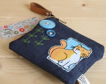 Portamonete o portatessere in jeans con applicazioni di gatto e bottoni. Jeans coincase with cute cat and buttons.