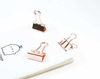 Set of 2 rose gold paperclips.