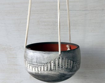 Handmade ceramic hanging planter in white and dark brown with carved stripes